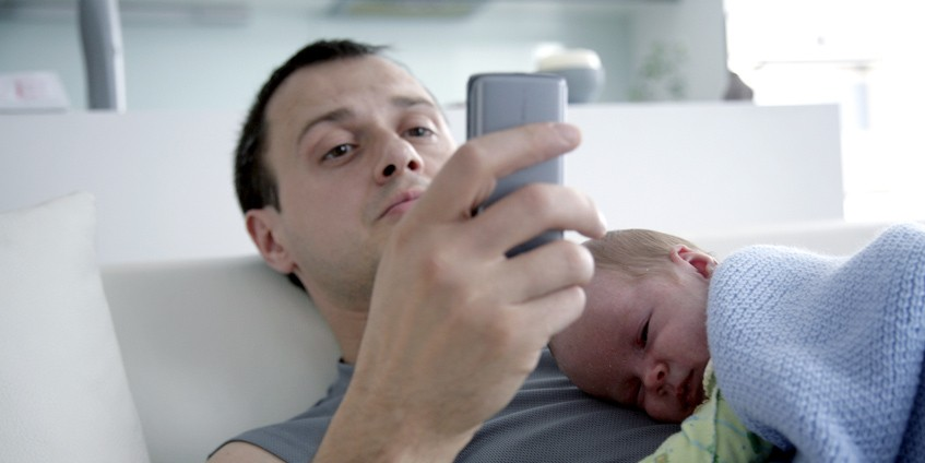 SMS4Dads promotional poster - Man holding baby whilst using phone