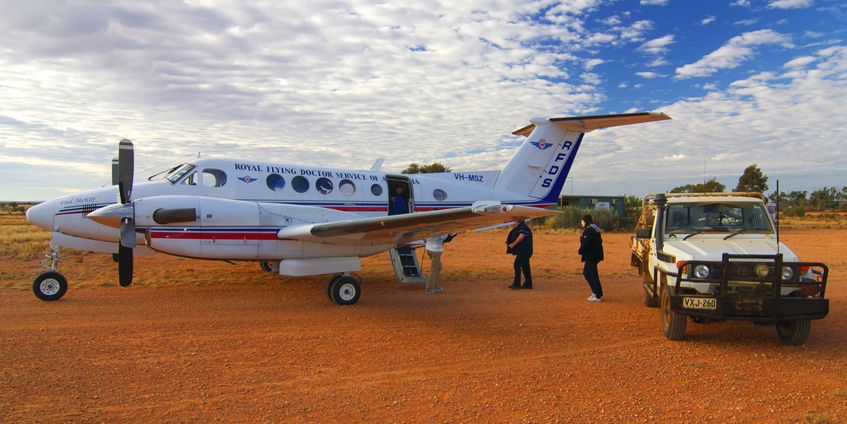 RFDS aircraft on red dirt runway with 4wd and two people aproaching plane