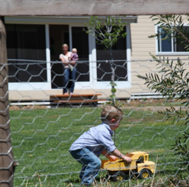 Boy playing with toy truck on front lawn
