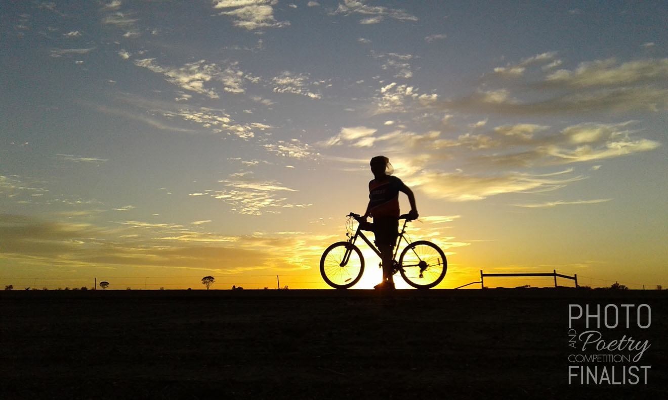 Dr Rimmer - Dr David Rimmer, Executive Director of Medical Services, Longreach, enjoys a glowing sunrise while cycling along the Old Muttaburra Road. David can often be spotted amongst a group of local riders. A typical weekend morning for these keen 'athletes' is to rendezvous before dawn, cycle out of town to meet the sunrise then return to Longreach for coffee and a yarn at one of the town's charming cafés. Could there be a better way to kick off a weekend? You might be hard pressed to convince Dr Rimmer and his bike-riding mates. LINDY RIXON, Longreach, QLD