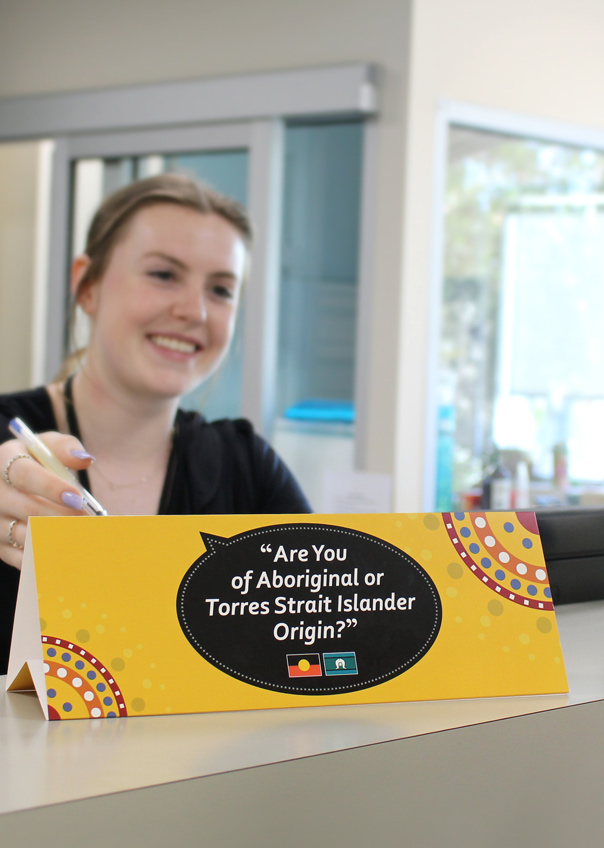 Woman pointing to sign that says are you of Aboriginal or Torres Strait Islander Origin