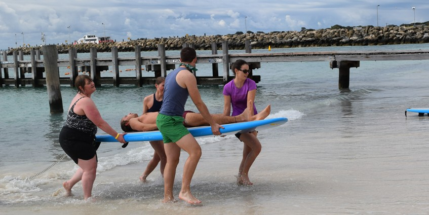 People carrying a person on a surfboard out of the ocean.