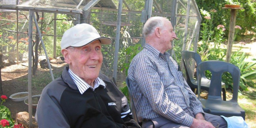Two male seniors sitting on a garden bench