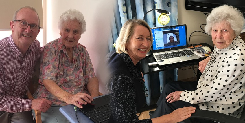 mature man and older mother using laptop younger and older women in front of computer