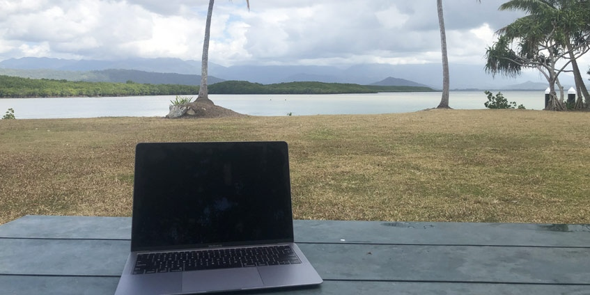 Laptop besides tropical coastline with palm trees