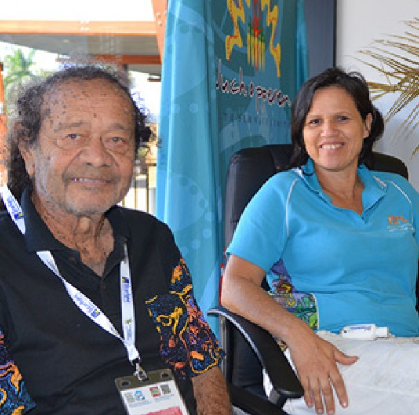 Man and woman seated Yirrkandji Elder, Georgie Skeenes with Wuchopperen staff members at the Culture, History and Healing stall at the recent conference