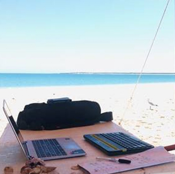 Laptop on camp table on the beach